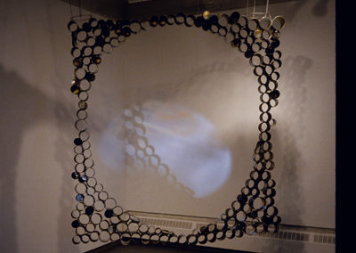 """<i>""""Squaring the Circle"""" </i>with video projection, Cans, 5' x 5' x 5"""", from <i>Transforming Matters</i>, Solo show; The Little Gallery, University of Calgary, Faculty of Fine Arts, Calgary, Alberta, Canada, 2002"""
