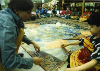 <i>Labour Ties; the Life of Iqbal Masih</i>,  in progress on floor, 1998, Oil on carpet, 8' x 12'<p><p> Teaching kindergarten students how to tie knots, Bancroft School, Montreal, Quebec.  The children also made handprints in paint on the carpet-canvas.