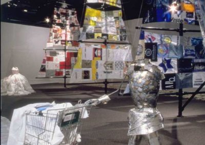 DETAIL:  Shopping bag sails on PVC-pipe masts, in background and tin-can armor knight with shopping cart, in foreground <p><p>From<i> LANDFILL AHOY!  The Journey of Lady Bag and the Everyday Knight</i>, 2003, Found object and sculptural installation with video, 50' x 50' x 22', The Nickle Arts Museum, Calgary, AB, Masters Thesis Show