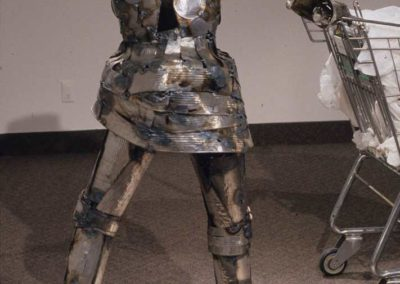 DETAIL:  Tin can armor knight with gauntlet<p><p><i>from LANDFILL AHOY!  The Journey of Lady Bag and the Everyday Knight</i>, 2003, Found object and sculptural installation with video, 50' x 50' x 22', The Nickle Arts Museum, Calgary, AB, Masters Thesis Show