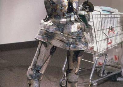 DETAIL:  Tin can armor with shopping cart <p><p><i>from LANDFILL AHOY!  The journey of Lady Bag and the Everyday Knight</i>, 2003, Found object and sculptural installation with video, 50' x 50' x 22', The Nickle Arts Museum, Calgary, AB, Masters Thesis Show